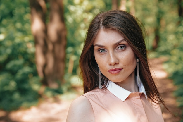 Portrait of beautiful woman posing on camera at green forest
