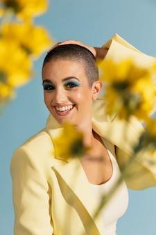 Ritratto di bella donna in posa con una giacca gialla e fiori