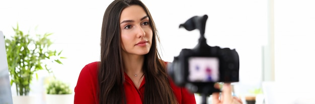 Portrait of beautiful woman in red giving interview in company office. smart brunette female employee talking on camera. worker holding clipboard. business meeting concept