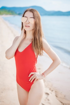 Portrait of beautiful woman in red swimsuit relaxing on the beach
