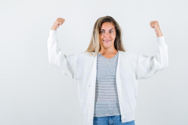 Ritratto di bella donna che mostra il gesto del vincitore in giacca e guardando felice vista frontale