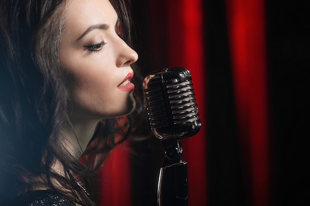 Portrait of beautiful woman singing in microphone