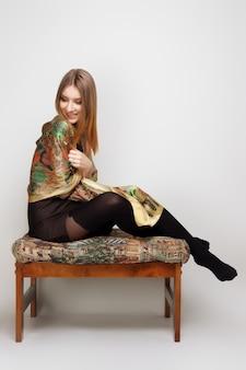 Portrait of beautiful woman sitting on ottoman