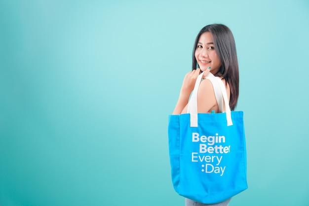 Портрет красивой женщины с улыбкой, держащей в руке эко ткань хлопчатобумажную сумку