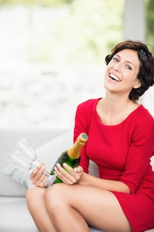 Portrait of beautiful woman smiling and holding champagne bottle and glass