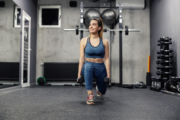 Portrait of a beautiful woman in sportswear and in good physical shape doing squats in an isolated indoor gym