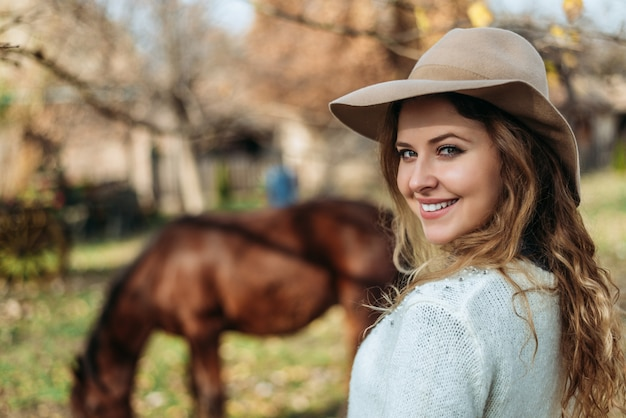 Portrait of beautiful woman standing outside near horse.