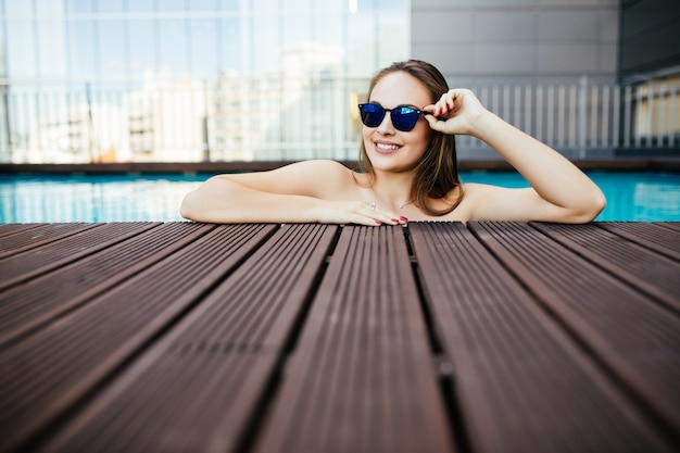 Portrait of a beautiful woman in sunglasses posing by the pool, summer day, outdoor