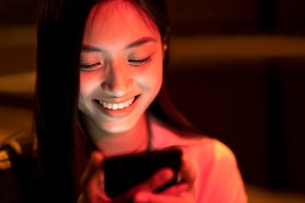 Ritratto di bella donna che utilizza smartphone di notte nelle luci della città