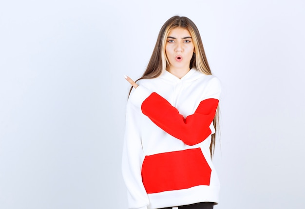 Portrait of a beautiful woman in warm hoodie standing and pointing away