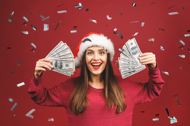 Portrait of beautiful woman wearing santa hat and holding dollar banknotes