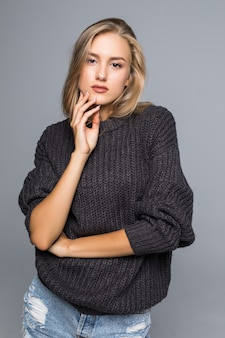 Portrait of a beautiful woman wearing a warm knit sweater on her body on a gray background isolated
