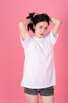 Portrait of beautiful woman wearing a white t-shirt on the pink.