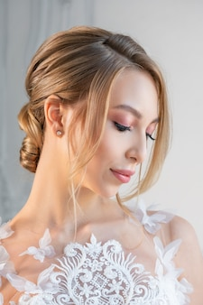 Portrait of a beautiful woman in a white wedding dress with a beautiful make-up and hairstyle