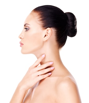Portrait of the beautiful woman who touches the neck by fingers