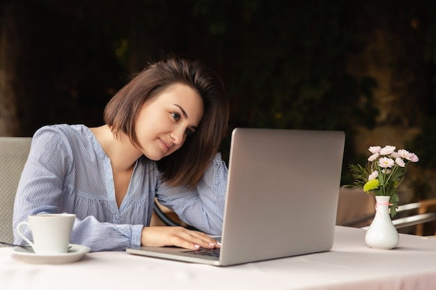 Portrait of beautiful woman who works from home, she sits with a cup of coffee at the table, working on laptop indoors