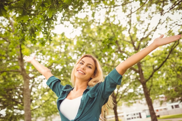 Portrait of beautiful woman with arms raised at park