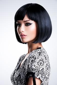 Ritratto di una bella donna con i capelli lisci neri e trucco da sera