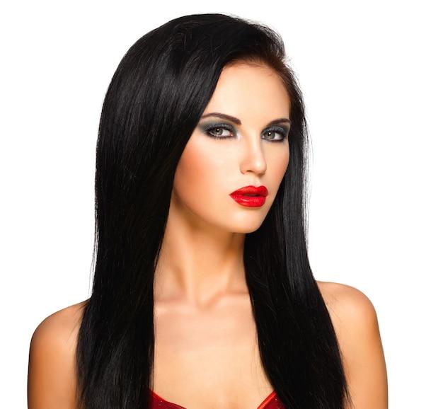 Ritratto di una bella donna con i capelli lisci neri e labbra rosse, trucco da sera