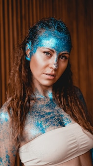 Portrait of beautiful woman with blue sparkles on her face in the bath. the concept of individuality