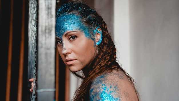 Portrait of beautiful woman with blue sparkles on her face. the concept of freaks and aliens. people are different from others. individuality