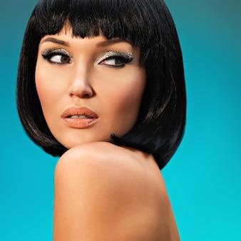 Ritratto di bella donna con acconciatura bob. fronte del modello di moda con trucco creativo