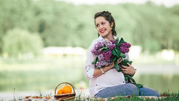 Portrait of a beautiful woman with a bouquet of lilacs