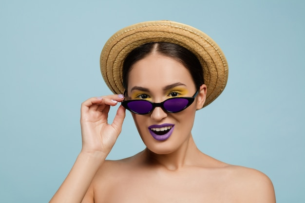 Portrait of beautiful woman with bright make-up, hat and sunglasses on blue studio background. stylish and fashionable make and hairstyle. colors of summer. beauty, ad concept. looks up of eyewear.