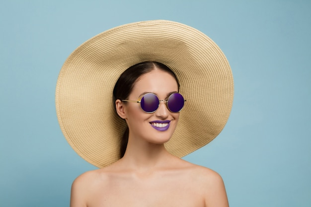 Portrait of beautiful woman with bright make-up, hat and sunglasses on blue studio background. stylish and fashionable make and hairstyle. colors of summer. beauty, fashion and ad concept. laughting.