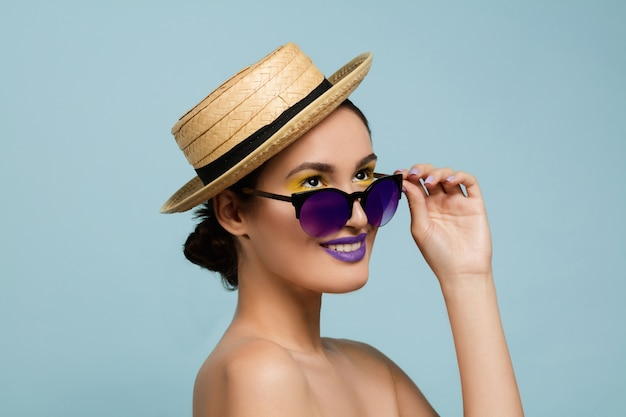 Ritratto di bella donna con trucco luminoso, cappello e occhiali da sole su sfondo blu studio. trucco e acconciatura alla moda e alla moda. colori dell'estate. concetto di bellezza, moda e annuncio. retrò.