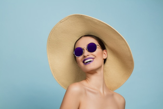 Portrait of beautiful woman with bright make-up, hat and sunglasses on blue studio