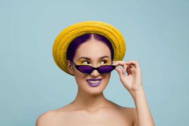 Ritratto di bella donna con trucco luminoso, cappello e occhiali da sole in studio blu