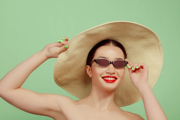 Portrait of beautiful woman with bright make-up, hat and sunglasses on green studio background. stylish and fashionable make and hairstyle. colors of summer. beauty, fashion and ad concept. smiling.