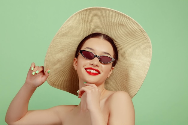Ritratto di bella donna con trucco luminoso, cappello e occhiali da sole su sfondo verde studio. trucco e acconciatura alla moda e alla moda. colori dell'estate. concetto di bellezza, moda e annuncio. sorridente.