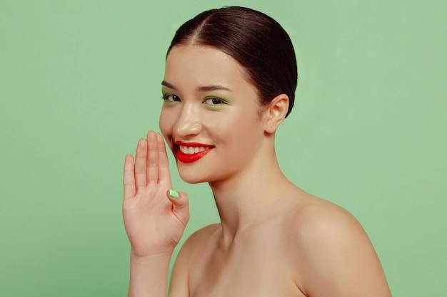 Ritratto di bella donna con trucco luminoso, occhiali rossi e cappello su sfondo verde studio. make, acconciatura alla moda e alla moda. concetto di bellezza, moda e annuncio. segreti sussurrati, vendite.
