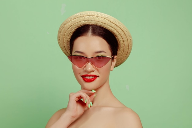 Portrait of beautiful woman with bright make-up, red eyewear and hat on green studio background. stylish and fashionable make and hairstyle. colors of summer. beauty, fashion and ad concept. posing.