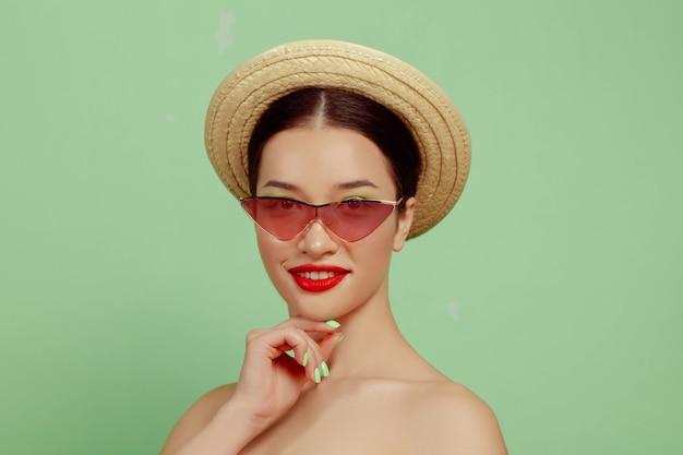 Ritratto di bella donna con trucco luminoso, occhiali rossi e cappello su sfondo verde studio. trucco e acconciatura alla moda e alla moda. colori dell'estate. concetto di bellezza, moda e annuncio. in posa.