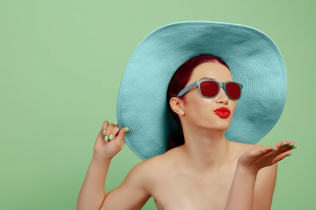 Portrait of beautiful woman with bright make-up, red eyewear and hat on green studio