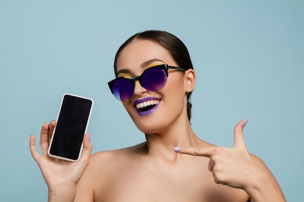 Ritratto di bella donna con trucco luminoso e occhiali da sole in studio blu