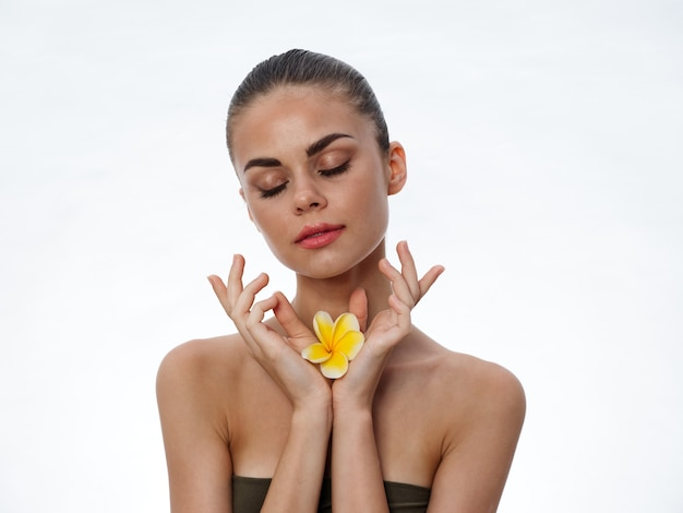 Portrait of a beautiful woman with closed eyes and a yellow flower in her hands