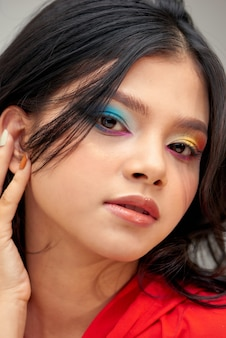 Portrait of a beautiful woman with color nails, rainbow makeup