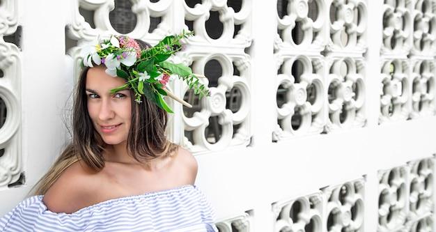 Ritratto di una bella donna con una composizione di fiori naturali sulla sua testa su uno sfondo chiaro.