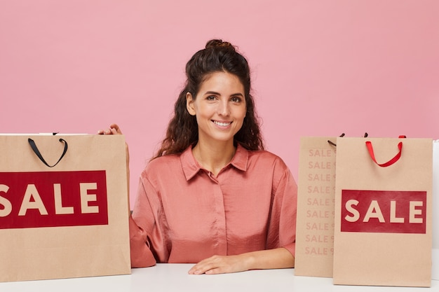 Portrait of beautiful woman with curly hair smiling at camera while sitting at the table with shopping bags