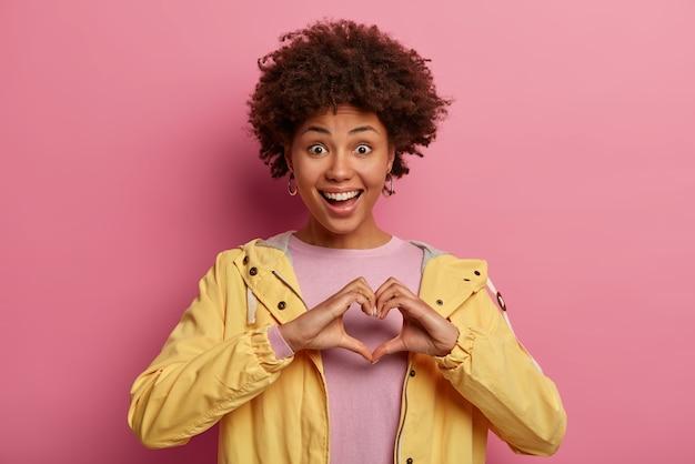 Ritratto di bella donna con l'acconciatura riccia fa il gesto del cuore sul petto, esprime amore, dice sii il mio san valentino, ha un'espressione positiva