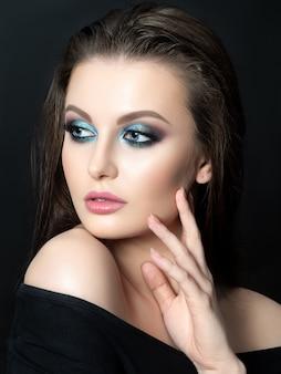 Portrait of beautiful woman with fashion makeup touching her face. modern blue smokey eyes make up.