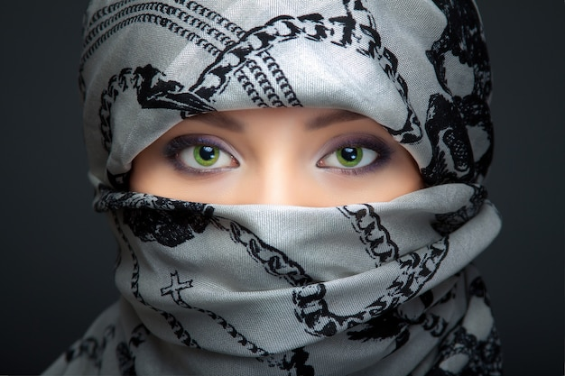 Portrait of beautiful woman with green eyes wearing gray scarf.