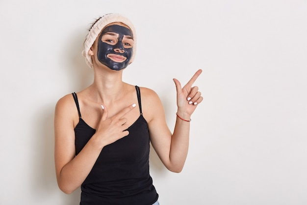 Portrait of beautiful woman with hairband on her head, has mud facial mask