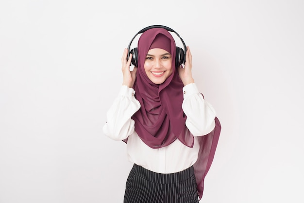 Portrait of beautiful  woman with hijab is enjoy listening music on white background
