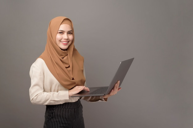 Portrait of beautiful woman with hijab is holding computer laptop on gray