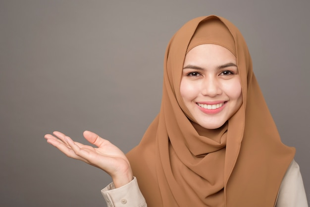 Portrait of beautiful woman with hijab is showing something on her hand